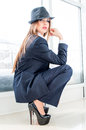 Beautiful business woman wearing man's suit, hat and high heels in office Royalty Free Stock Photo