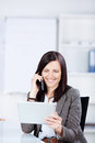 Beautiful businesswoman calling while looking at her tablet Royalty Free Stock Photos