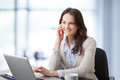 Beautiful businesswoman having a phone conversation modern working on her laptop in office and Royalty Free Stock Photo