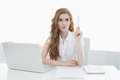 Beautiful businesswoman with laptop pointing upwards young at desk in a bright office Royalty Free Stock Photography