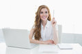 Beautiful businesswoman with laptop pointing upwards young at desk in a bright office Royalty Free Stock Image