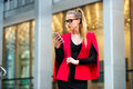 Beautiful businesswoman texting outside the office on mobile phone Royalty Free Stock Photo