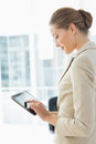 Beautiful businesswoman using digital tablet in office side view of a young a bright Royalty Free Stock Photos