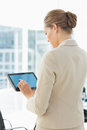 Beautiful businesswoman using digital tablet rear view of a young in a bright office Stock Photography