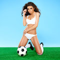 Beautiful busty female soccer player in white sport lingerie and boots kneeling on a green and blue background with a ball Stock Photos