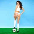 Beautiful busty woman soccer player in lingerie with long curly brunette hair posing with a ball blue and green studio Royalty Free Stock Photography
