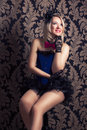 Beautiful cabaret woman posing on a chair against retro wallpape Royalty Free Stock Photo