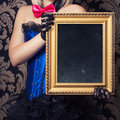 beautiful cabaret woman posing with golden frame against retro w Royalty Free Stock Photo