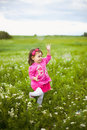 Beautiful carefree girl playing outdoors in field with high green grass little child running away from bubbles and laughing Royalty Free Stock Photo
