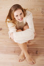 Beautiful carefree young casual woman sitting on the floor wooden Royalty Free Stock Photos
