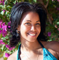 Beautiful caribbean brunette posing against pink flowers close up Royalty Free Stock Photos