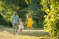 Caring parents holding hands of daughter while walking together in the park Royalty Free Stock Photo