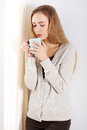 Beautiful casual caucasian woman standing by the window with hot drink coffee or tea indoor background Stock Photography
