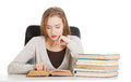 Beautiful casual student woman sitting by stack of books and lea Royalty Free Stock Photo