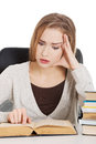 Beautiful casual woman student worried scared is sitting by a d desk and stack of books isolated on white Royalty Free Stock Images