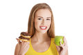 Beautiful caucasian casual woman with doughnuts and apple. Royalty Free Stock Photo