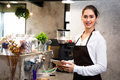 Beautiful Caucasian female barista using tablet and smiling inside coffee shop Royalty Free Stock Photo