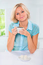 Beautiful caucasian female sitting at table and drinking coffee in bright room Royalty Free Stock Photography