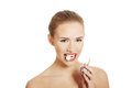 Beautiful caucasian topless woman with raw garlic in mouth. Royalty Free Stock Photography