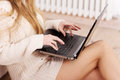 Beautiful caucasian woman in bright sweater is writing on laptop indoor background Stock Photo