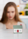 Beautiful caucasian woman and small house model focus on indoor background Stock Image