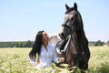 Beautiful caucasian young woman and horse portrait at the field with flowers Stock Photography