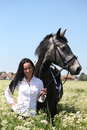 Beautiful caucasian young woman and horse portrait at the field with flowers Stock Images