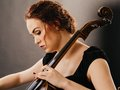 Beautiful cello player closeup photo of a woman playing a Royalty Free Stock Photography