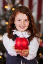 Beautiful charming little christmas girl holding out a red bauble in her cupped hands with a serene smile Stock Photo