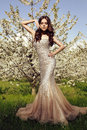 Beautiful charming woman in luxurious sequin dress fashion outdoor photo of posing blossom spring garden Stock Photo