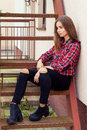 Beautiful charming young attractive girl with large blue eyes with dark long hair in autumn day sitting on the stairs black Royalty Free Stock Photos