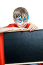 Beautiful cheerful child dressed as superman holds a rectangular black board with space for text Stock Image
