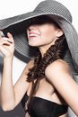 Beautiful cheerful girl in a summer beach striped hat. The beauty of the face. Royalty Free Stock Photo