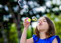 Beautiful child blowing bubbles in a meadow with greenery in the background Stock Photography