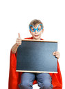 Beautiful child dressed as superman holds a rectangular black board smiling cheerful with space for text showing thumbs up and Royalty Free Stock Photos