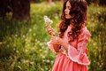 Beautiful child girl dressed as fairytale princess playing with blow balls in summer forest curly Royalty Free Stock Photo