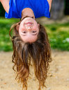 Beautiful child hanging upside with greenery in the background Stock Image