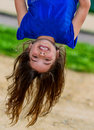 Beautiful child hanging upside and laughing with greenery in the background Stock Images