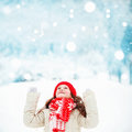 Beautiful child stretches her hand to catch falling snowflakes. Royalty Free Stock Photo