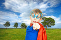 Beautiful child superhero standing on summer field background wearing a cape against with trees and clouds looking strong and Royalty Free Stock Photos