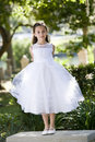Beautiful child in white dress on park bench Royalty Free Stock Image