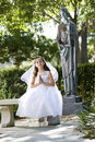 Beautiful child in white dress sitting on bench Stock Images