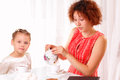Beautiful child and young girl drinking tea Royalty Free Stock Photos