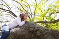 Beautiful children kid girl resting lying on a tree Royalty Free Stock Photo