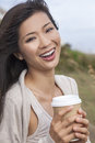 Beautiful chinese asian woman girl drinking coffee outdoor portrait of a young young or with perfect teeth takeaway Stock Photography