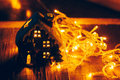 Beautiful Christmas decoration with tangerines and a toy house in the night light garlands. Citrus still life Royalty Free Stock Photo