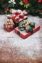 Beautiful Christmas and new year gift boxes on wooden board, pine branches with ornaments background. Motion of snow falling and