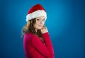 Beautiful christmas woman portrait of attractive isolated on blue studio shot in hat Royalty Free Stock Photos