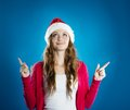 Beautiful christmas woman portrait of attractive isolated on blue studio shot in hat Stock Photos