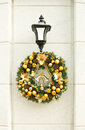 Beautiful christmas wreath golden balls bells pine cones hanging lantern white stone wall street traditional festive decorations Royalty Free Stock Image